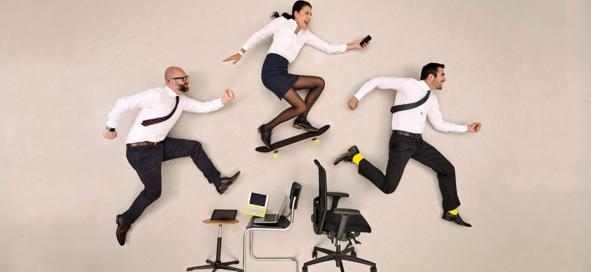 Office workers leap with enthusiasm over their workstation.