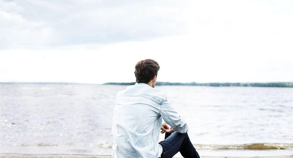 A man gazes at the water.