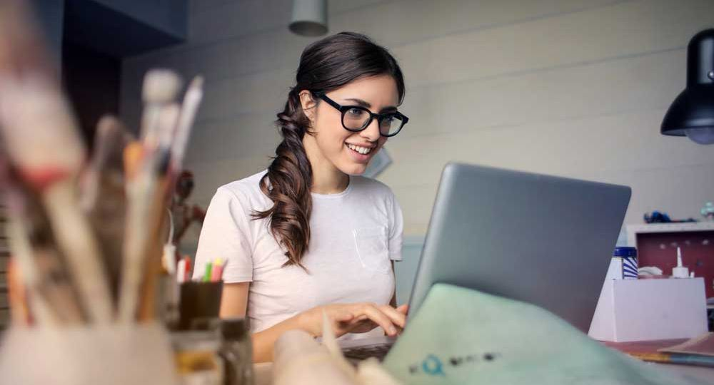 A brunette woman in glasses works on her laptop.
