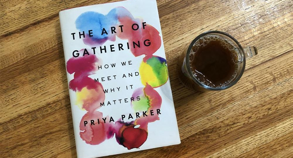 The book The Art of Gathering with cup of coffee