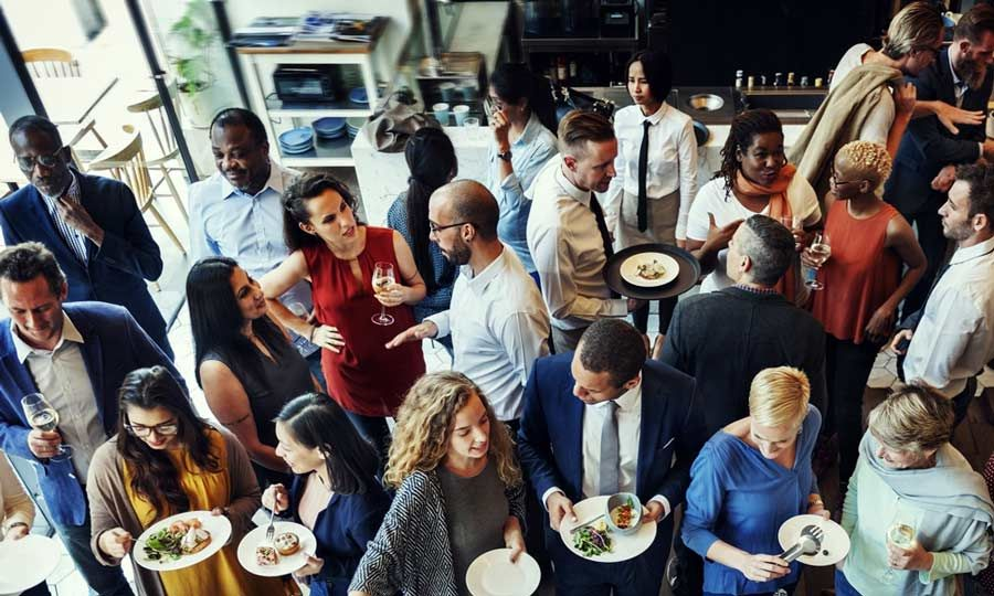 An overhead view of several people networking.