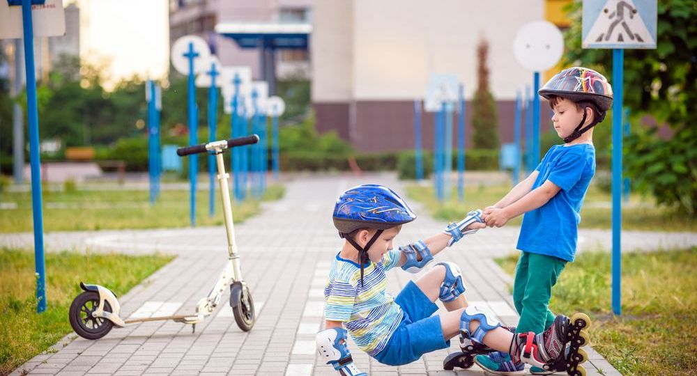 A boy helps another boy up after falling off his scooter.