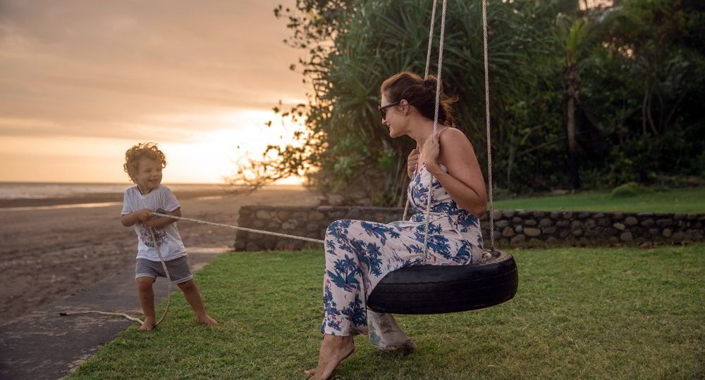 A young boy leisurely pulls his mother on a swing at sunset.