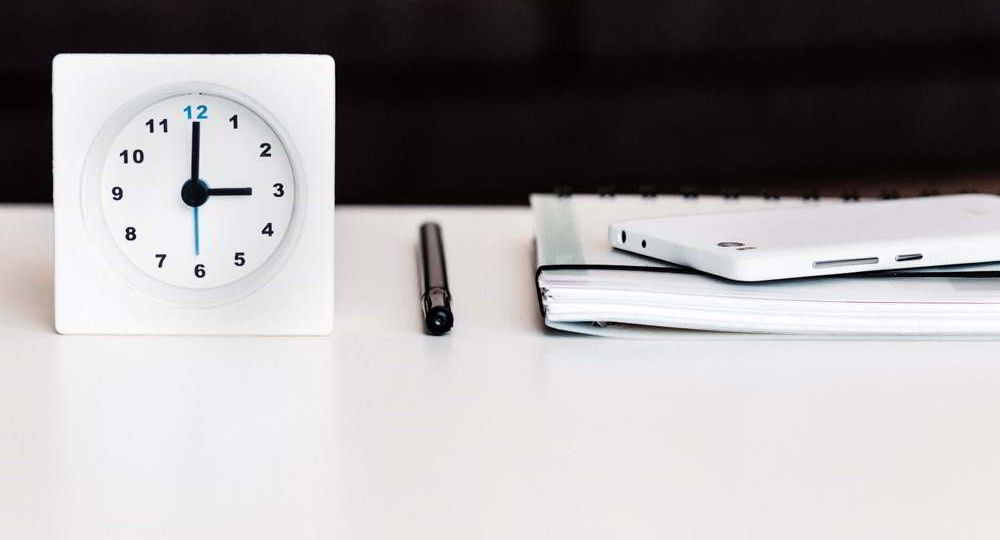 A worktop surface including a clock, plannter, phone, and pen.