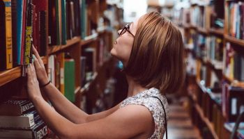 A woman looks up curiously at books on a shelf.