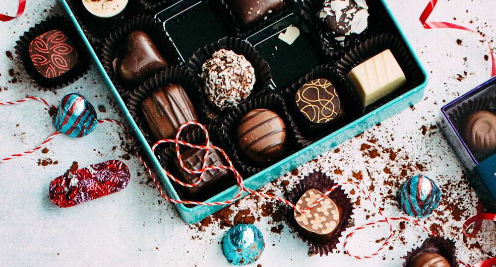 An overhead view of a box of gift chocolates displayed artistically.