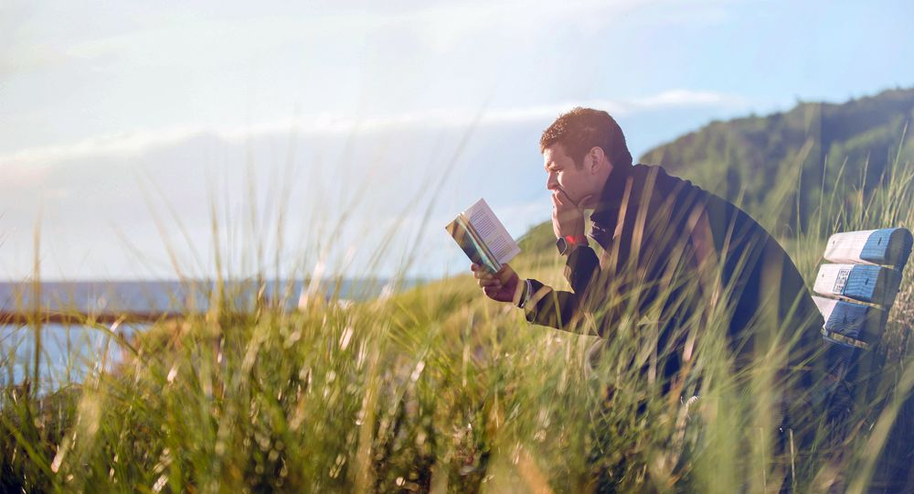A man reads a book while sitting on a bench in tall grass near the water.